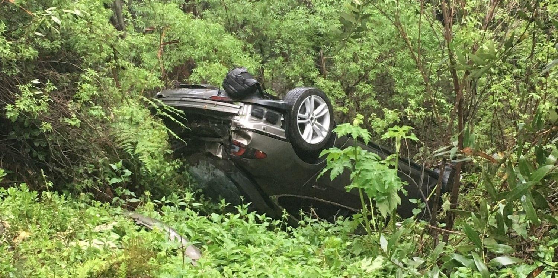 Tesla Model S upside down in a trail